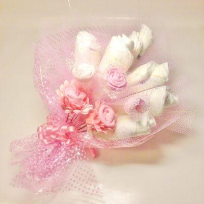 Blöjbukett flicka i rosa. Sedan några år tillbaka är det förbjudet att besöka sjukhus med riktiga blommor. Med denna blöjbukett är det fritt fram att besöka sjukhus då den inte doftar eller innehåller något allergi framkallande som inte är lämpligt på sjukhus när man kommer med en present och vill överraska de nyblivna föräldrarna. Blöjbukett flicka innehåller 6 st Libero newborn blöjor (kan ändras), 2 st blommor gjorda av newborn sockar och 3 st skumgummi rosor. inslagen i cellofan, dekorationsnät och matchande band.