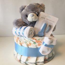 Snygg neutral blöjtårta i grått. Denna blöjtårta är en passande present till babyshower när du ännu inte vet könet på den kommande bäbisen och ändå behöver köpa en present som är rätt och blir uppskattad. Neutral blöjtårta går i grått så den passar både till om det blir en ficka eller en pojke. Innehåller blöjor från Libero, en babyhandduk, ett par babysockor, ett manikyrset bestående av en babyvänlig sax och nagelklippare och så förstås den söta grå teddybjörnen.
