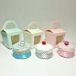 Present i form av en tvätthandduk formad som en cupcake lämplig som rolig gåva på babyshower eller dop. Cupcake av tvätthandduk, dekorerad med glittrig bomullsboll och lindad med fint prickigt satinband med tillhörande cupcake låda. Överraska med denna läckra babygåva. Välj mellan Vit, Rosa eller Blå. Tvätthandduk storlek: 30x30 cm